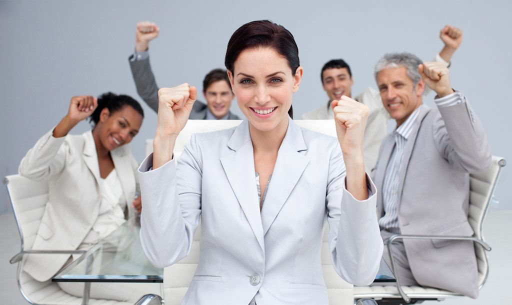 Happy business people celebrating a sucess with hands up in the office